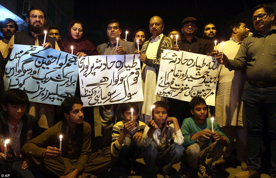 Members of a civil society group hold candles during a vigil for the victims of the plane crash, which was held in Multan